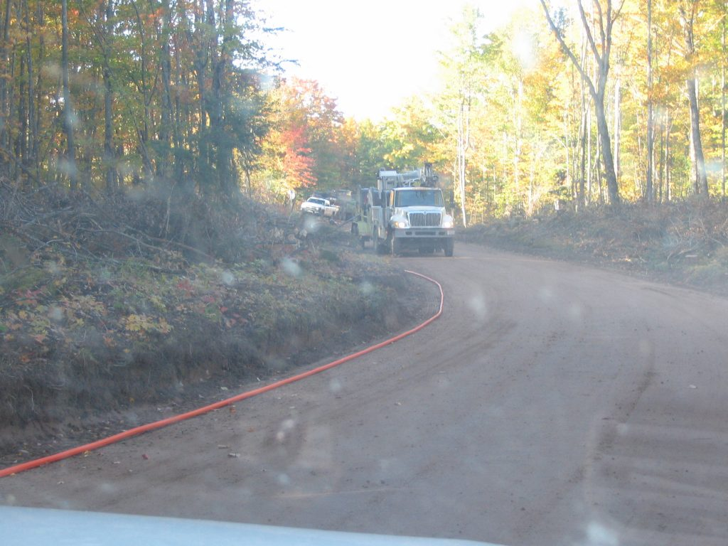 Contractors laying cable on AAA road to power mine facility